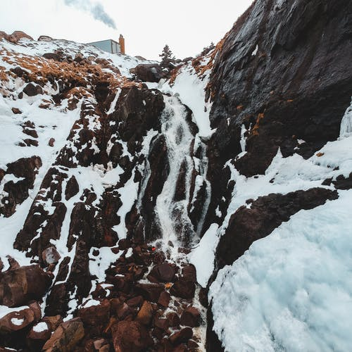 Cold waterfall on high mountain cliff