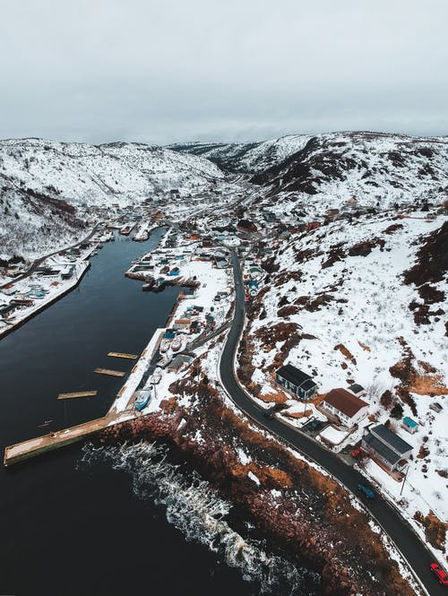 Drone view of port village with piers alongside rocky coast of harbor with buildings and road in snow