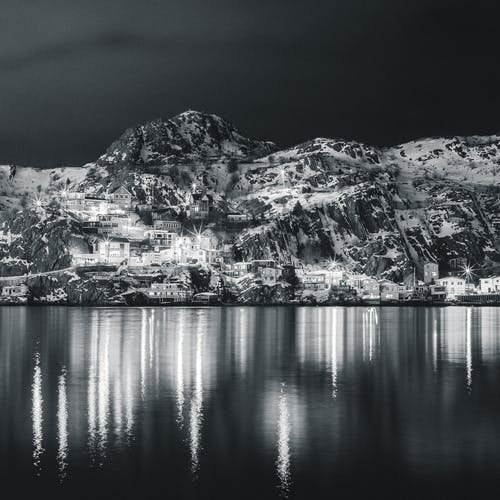 Black and white glowing town on shore of peaceful bay with mountains reflecting in dark water at night