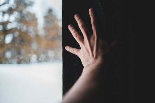 Tender hand on background of black wall reaching out near window with view of woods in winter