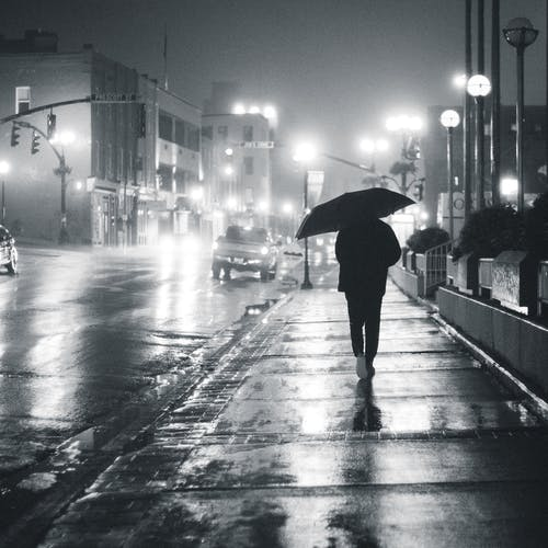 Silhouette of person with umbrella walking on wet sidewalk with glowing lamps and cars at night