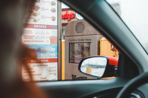 Person ordering fast food in drive thru