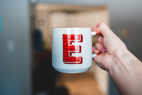 Hand of person holding white ceramic cup with tartan letter E at home