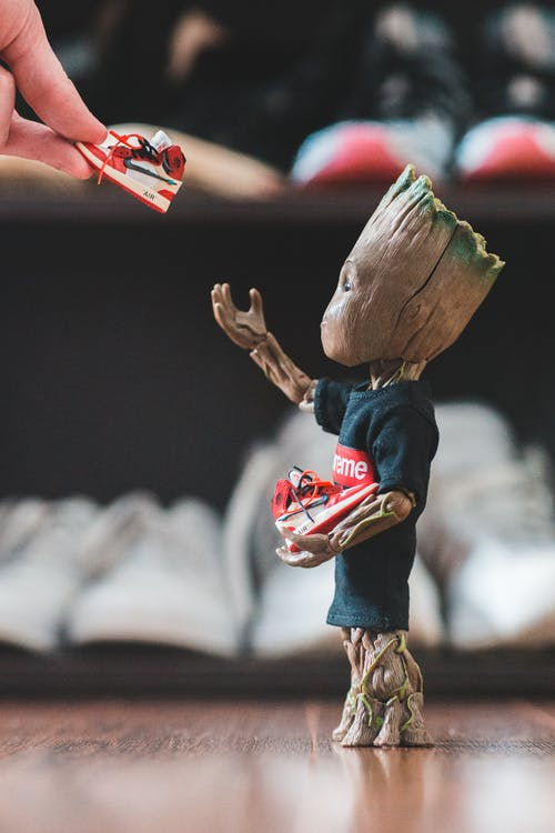 Crop fan giving small sneakers to small plastic comic tree character dressed in t shirt