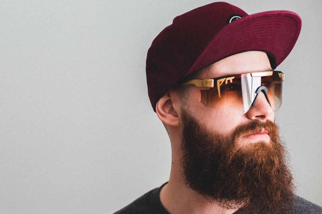 Portrait of young bearded man in cap and golden sunglasses looking away on gray background