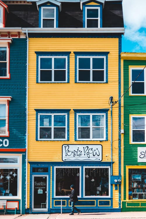 Man Passing By Colorful Buildings