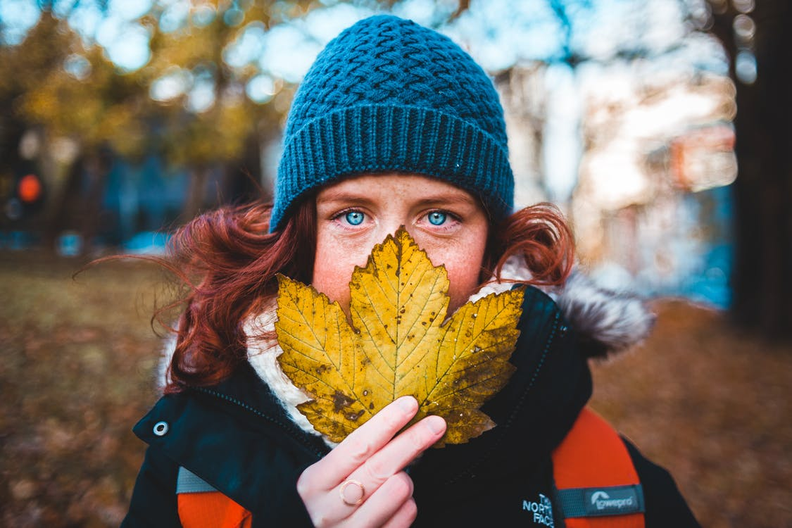 Girl in Black Knit Cap Holding Yellow Maple Leaf