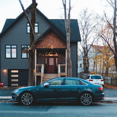 Black Sedan Parked Beside Brown Wooden House