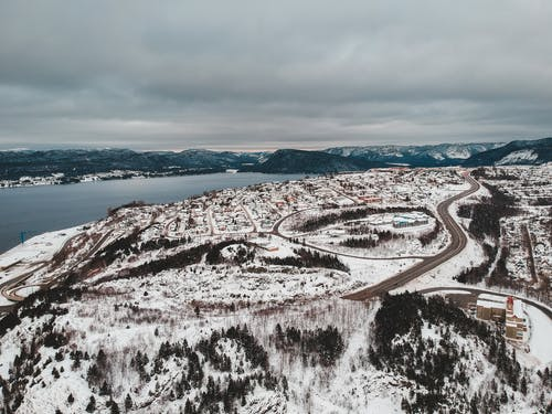 Aerial View of Snow Covered Mountain Near Body of Water