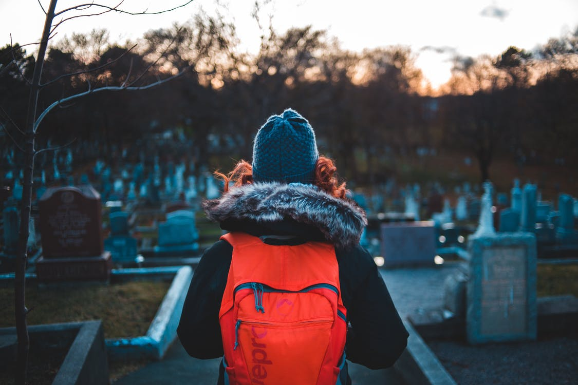 Person in Blue Knit Cap and Red Backpack Standing on Graveyard