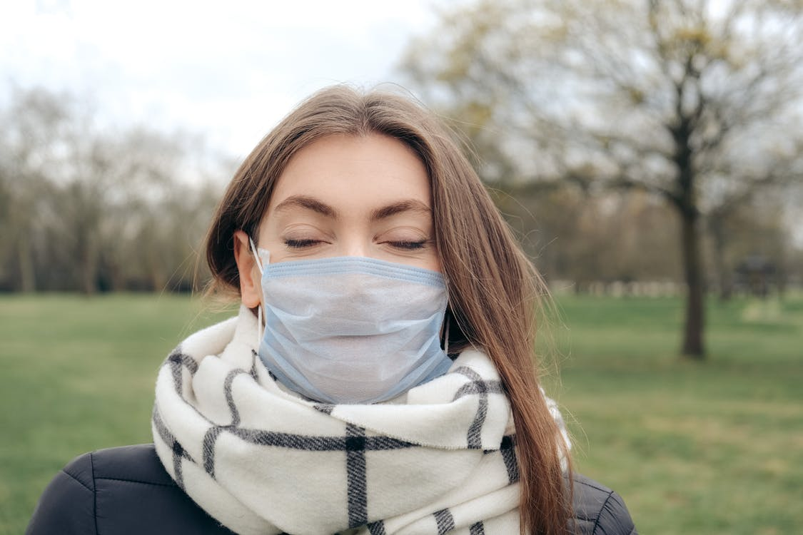 Woman in White Scarf and Black Jacket with Face Mask