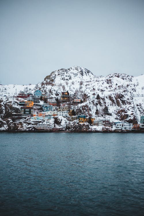 Houses on Snow Covered Mountain Near Body of Water