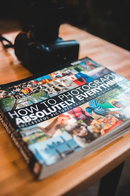 Colorful book with pictures near photo camera on table