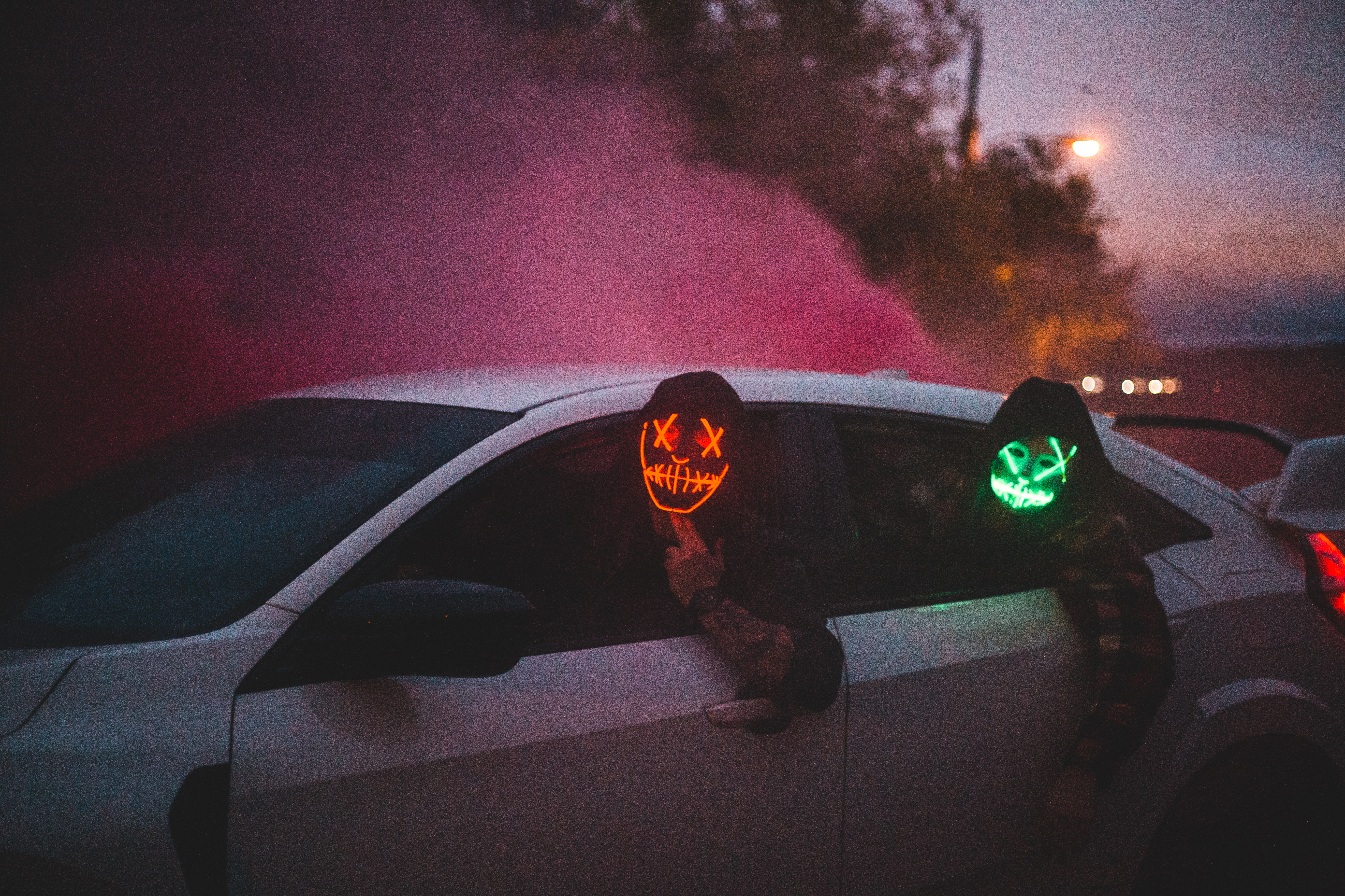 Unrecognizable Men In Glowing Halloween Masks Driving Car At Night Free Stock Photo Anonymous mask guy white car road