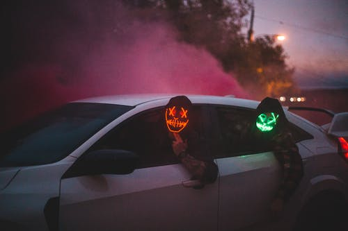 Unrecognizable men in glowing Halloween masks driving car at night