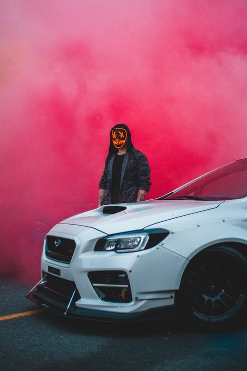 Unrecognizable man standing near modern car and bright dusty cloud