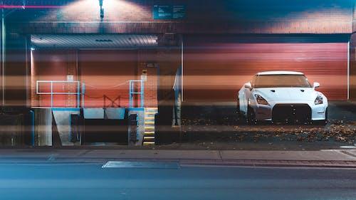 Ingyenes stockfotó autó, éjszaka, építészet, fehér autó témában