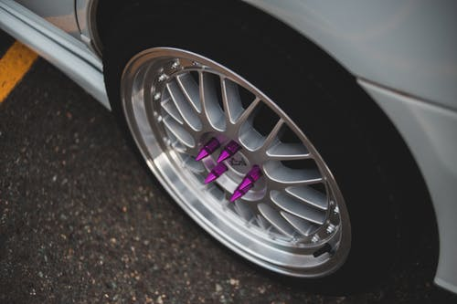 From above of contemporary design automobile wheel with purple stainless bolt spikes parked on asphalt pavement in daylight
