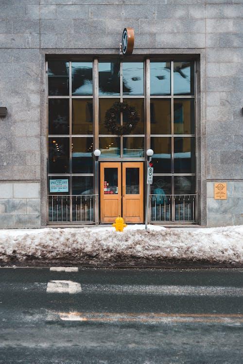 Brown Wooden Door on Gray Concrete Building
