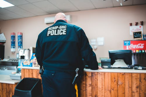 Police Man Standing Infront Of A Counter In A Restaurant