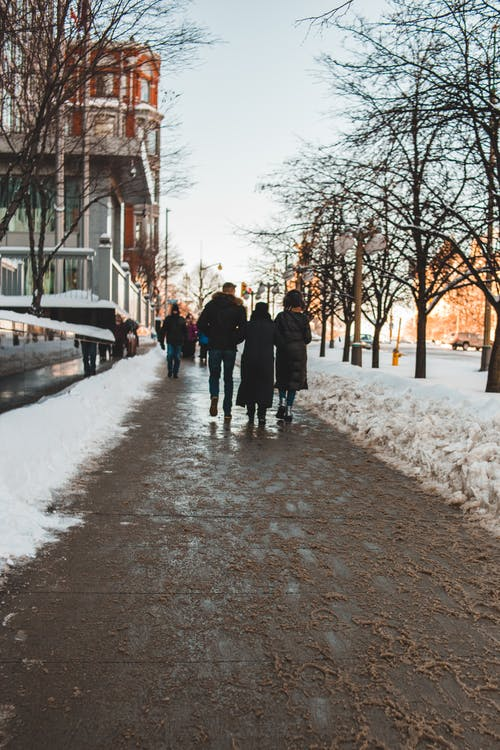 People Walking on Snow Covered Pathway