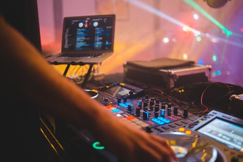 Dj with mixer controller in night club