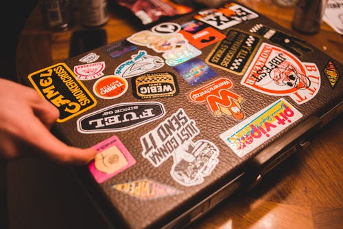 Black suitcase with stickers placed on table