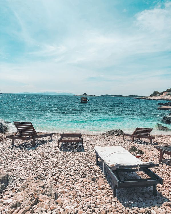 Brown Wooden Chairs on Beach