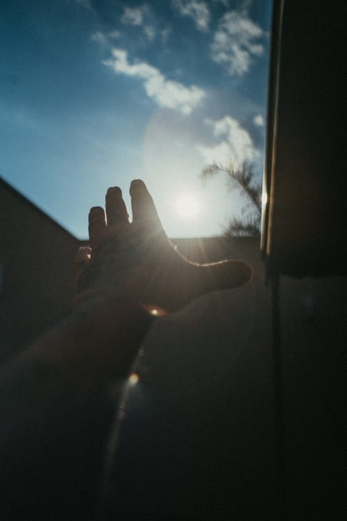 Persons Left Hand With Blue Sky and White Clouds
