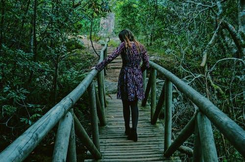 Woman in Purple and Black Dress Walking on Wooden Bridge