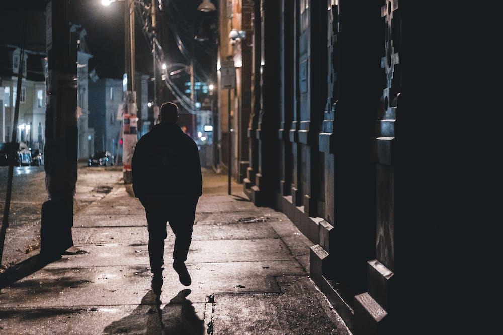 Man walking on sidewalk at night.   Photo: Pexels