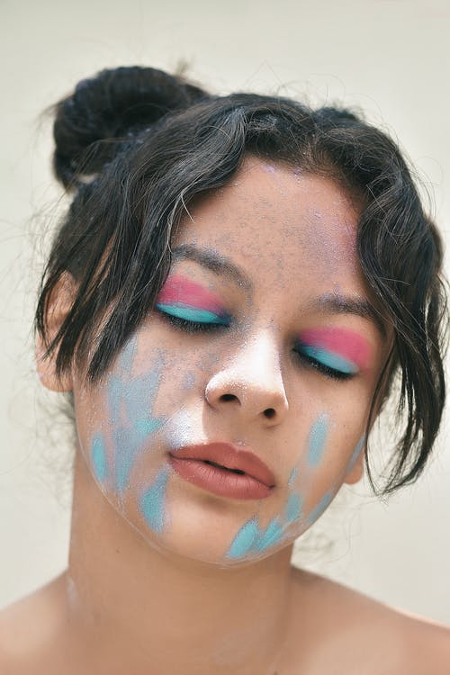 Young mindful ethnic female teenager with dirty face and makeup on closed eyes with tilted head on light background