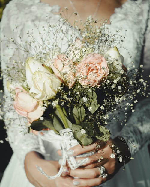Crop anonymous elegant woman in bridal dress and rings with rose bouquet during festive event