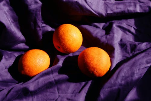 Orange Fruit on Purple Textile