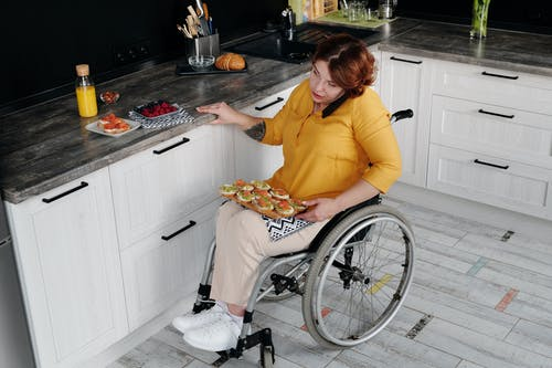 Woman in Wheelchair Using Phone in Kitchen
