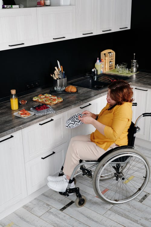 Woman in Yellow T-shirt Sitting on Wheelchair