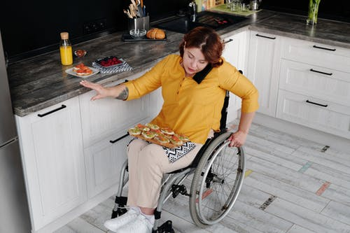 Woman in Yellow Long Sleeve Shirt Sitting on Wheelchair