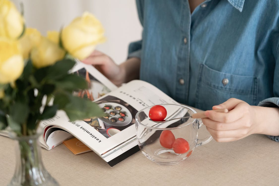 Person in Blue Button Up Shirt Eating Cherry Tomatoes