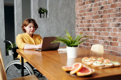 Woman in Yellow Long Sleeve Shirt Sitting on Chair in Front of Macbook