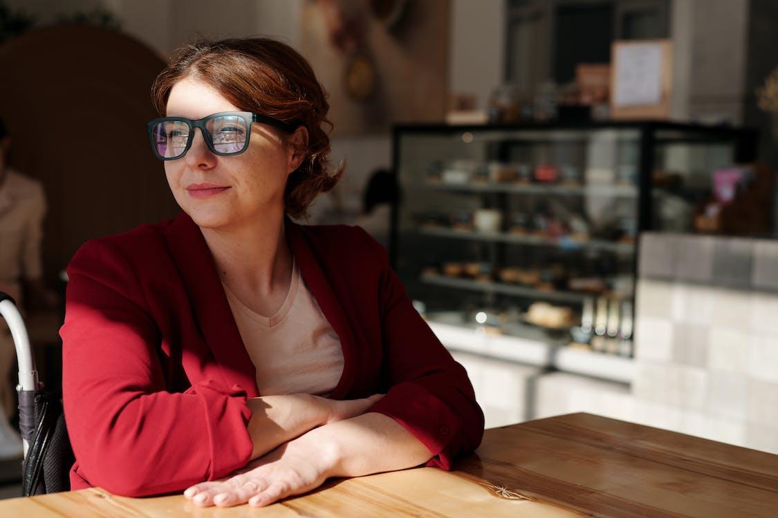 Woman in Red Long Sleeve Shirt Wearing Black Framed Eyeglasses