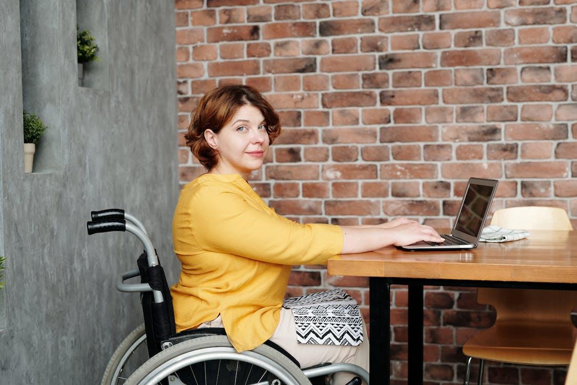 Woman in Yellow Long Sleeve Shirt Sitting on Black Wheelchair