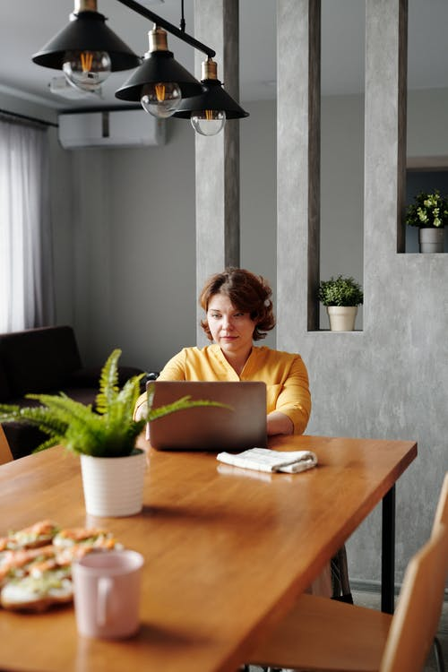 Woman in Yellow Long Sleeve Shirt Typing on Her Laptop