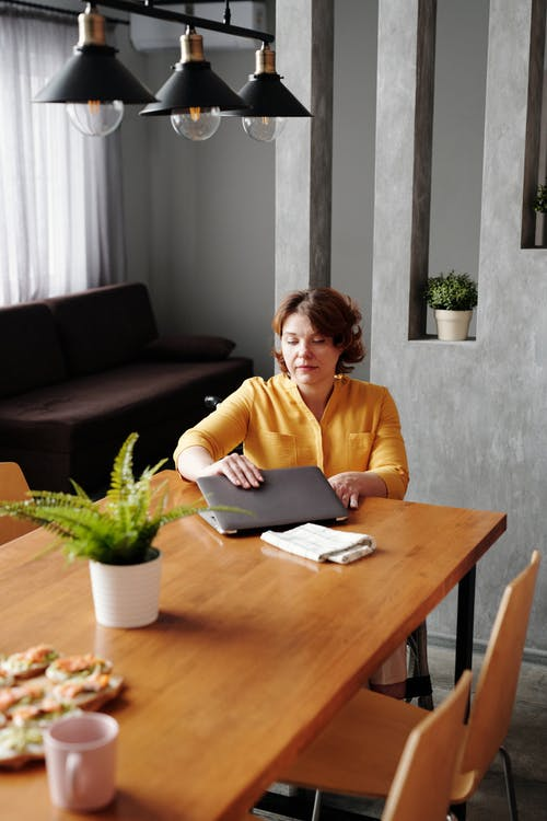 Woman in Yellow Long Sleeve Shirt Finish Working on Her Laptop