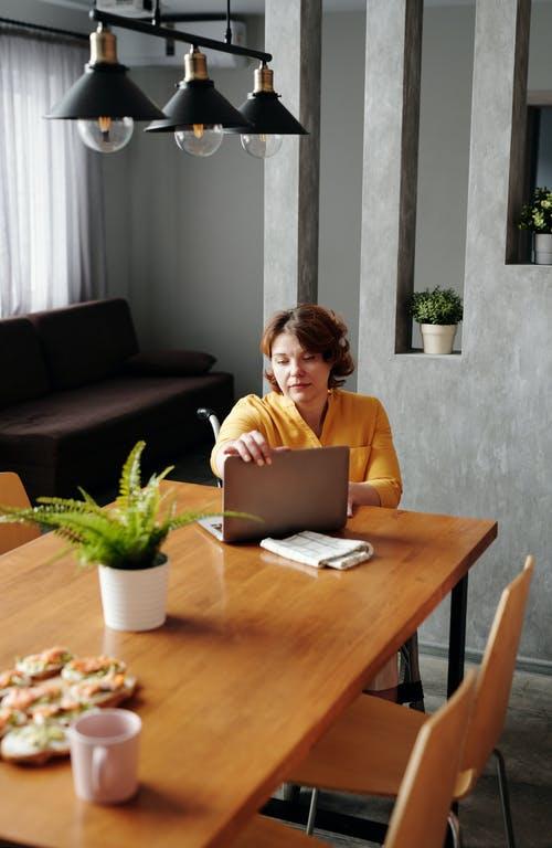 Woman in Yellow Long Sleeve Shirt Holding Her Laptop