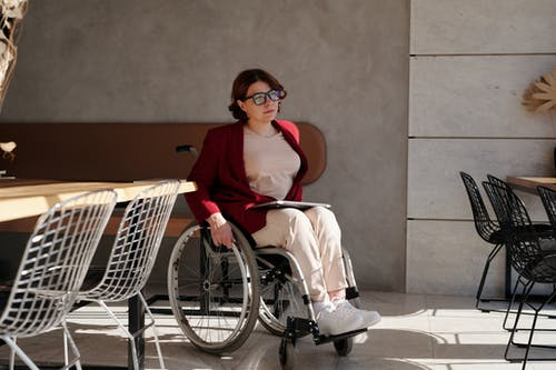Woman in Red Blazer Top and White Pants Sitting on Wheelchair