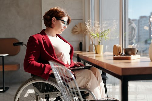 Woman in Red Blazer Sitting on Wheelchair in Front of Table
