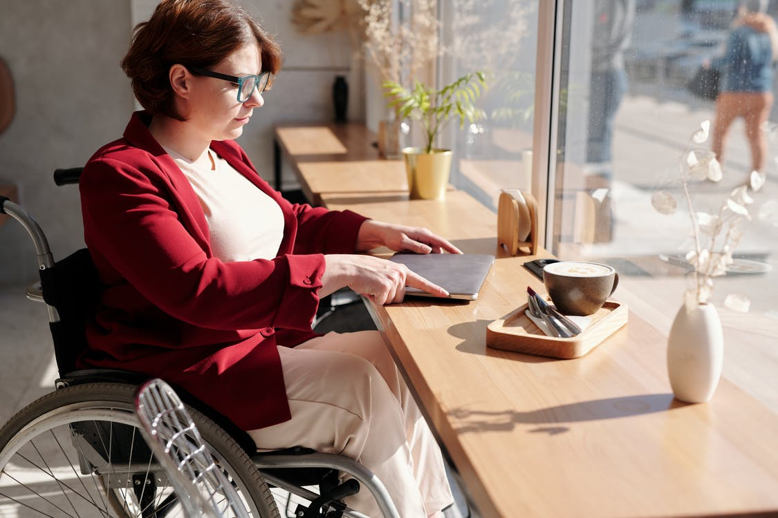 Woman in Red and White Long Sleeve Shirt Sitting on Wheelchair