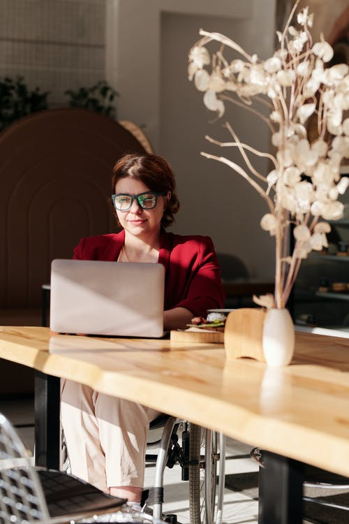 Woman in Red Long Sleeve Shirt Wearing Black Framed Eyeglasses Using Macbook