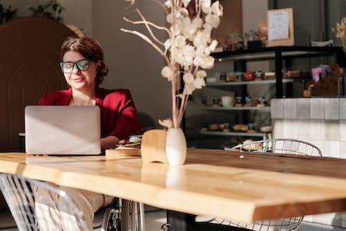 Woman in Red Long Sleeve Blazer Wearing Black Framed Eyeglasses Using Laptop