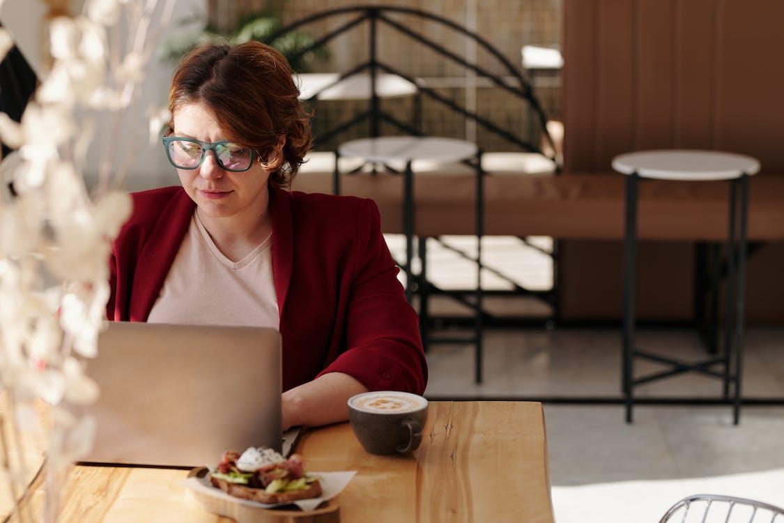 Woman in Red Blazer Using Laptop
